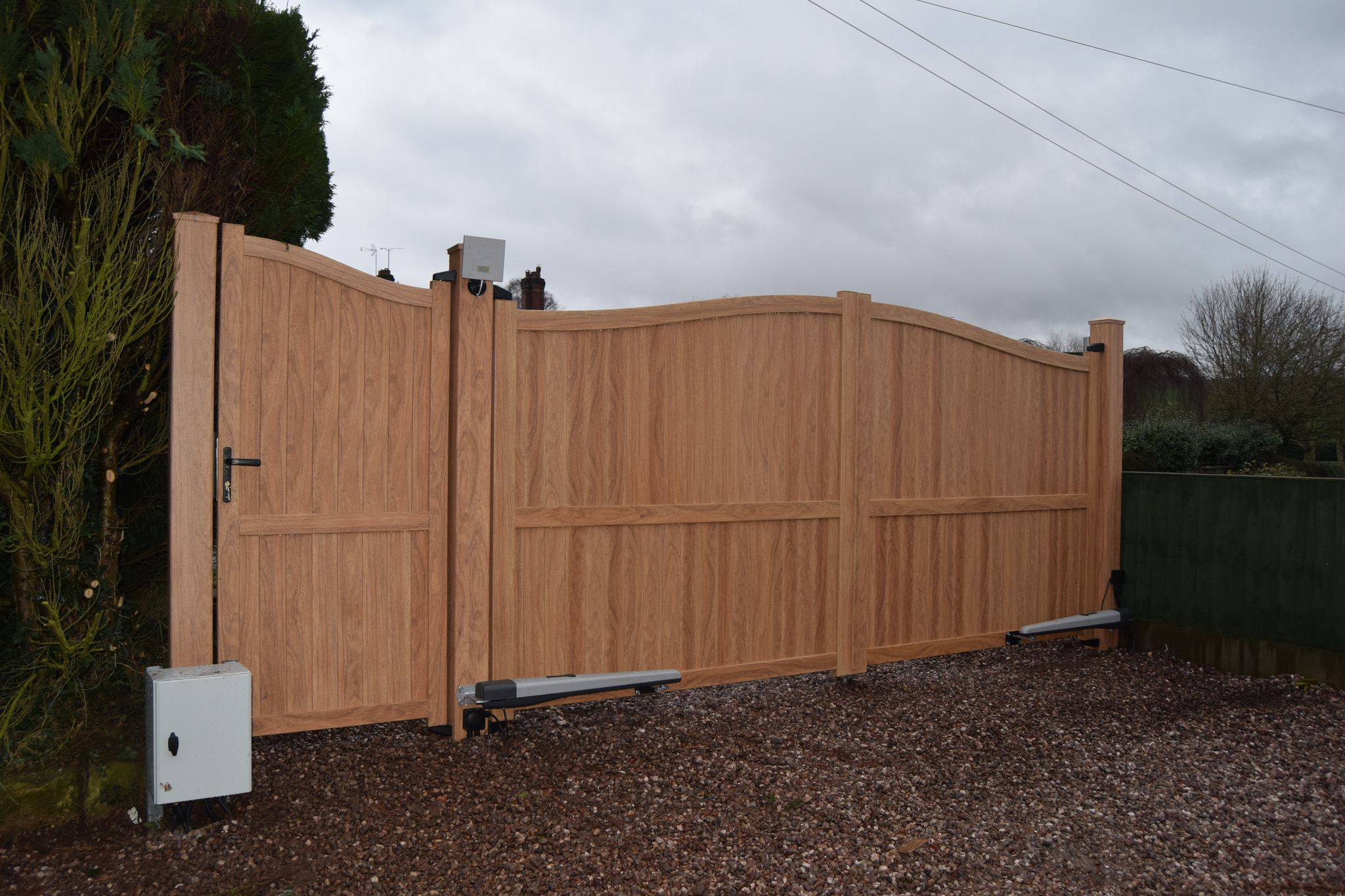 Double aluminium drive gates and matching side gate painted in woodgrain effect light oak finish