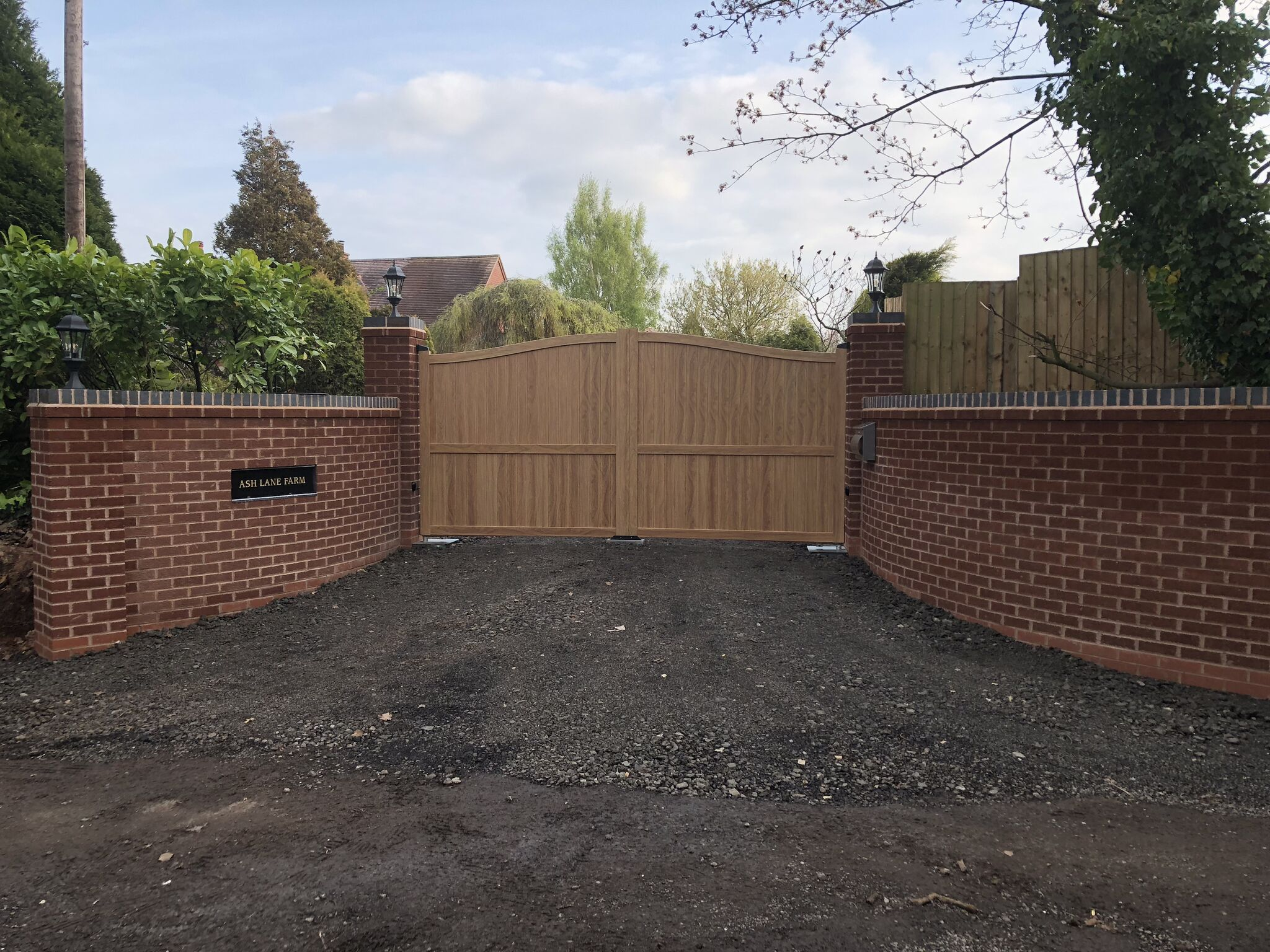 Modern aluminium driveway gates painted with a woodgrain finish