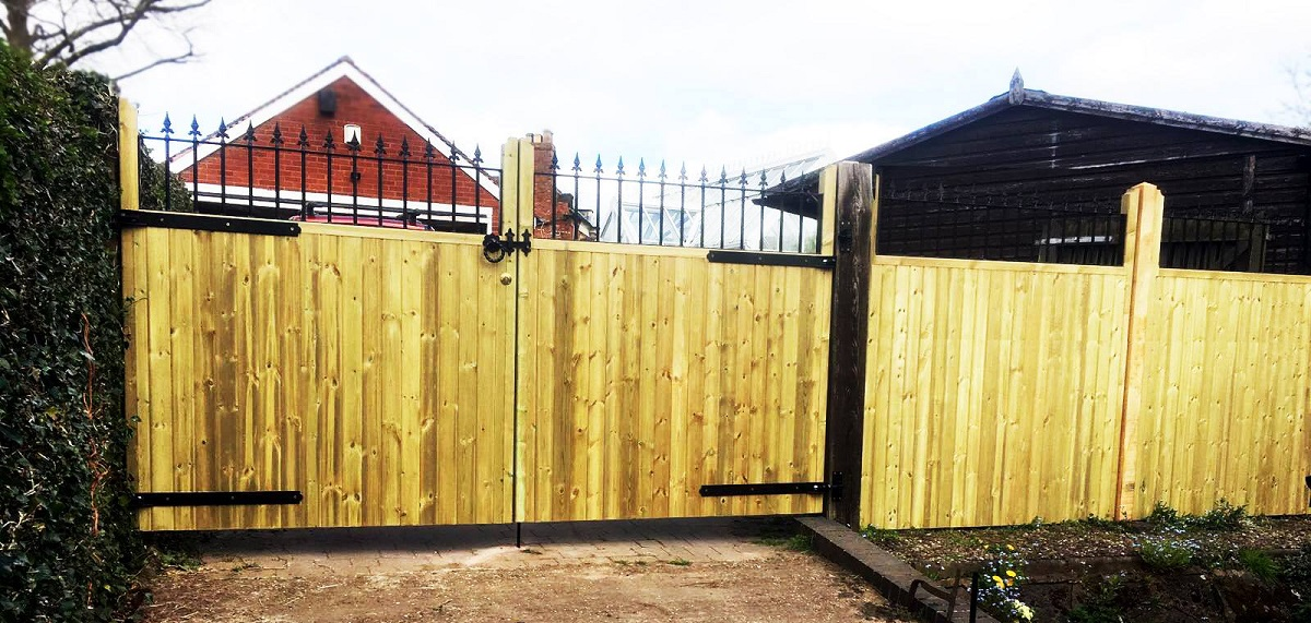 Custom made wooden estate gates and fence with decorative metal top rails
