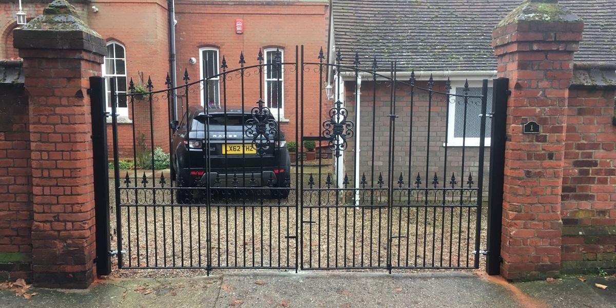 Royal premier bi folding driveway gates mounted to large brick pillars
