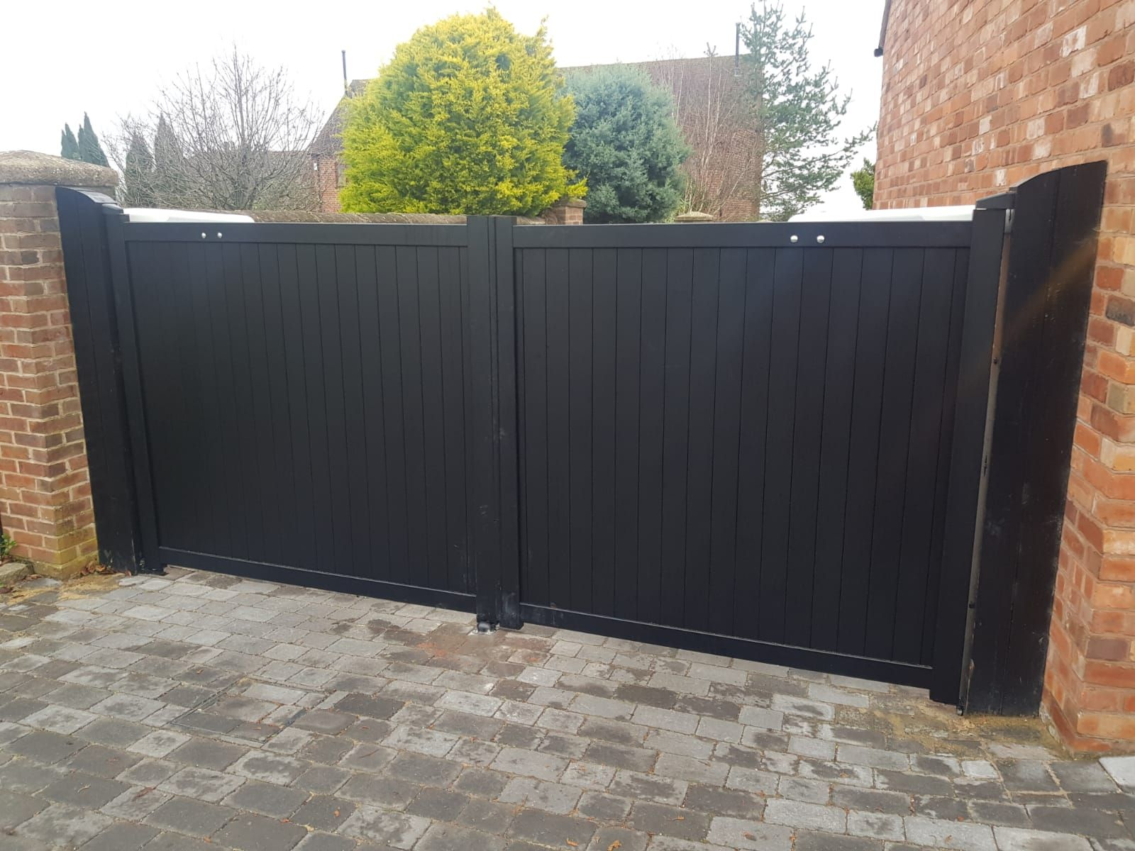 Black vertical panel aluminium drive gates fitted to brick pillars