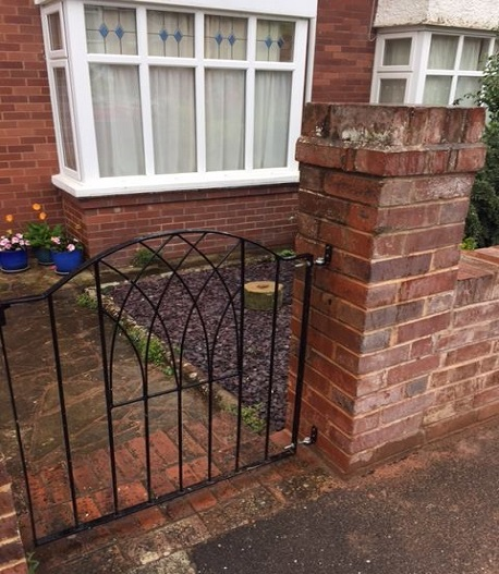 Garden gate mounted directly to brick pillars