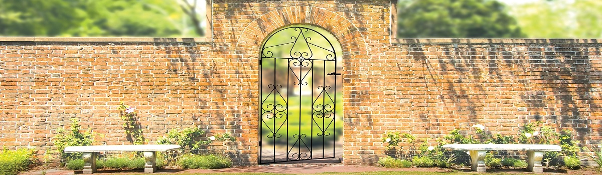 Arch top metal side garden gate fitted to brick wall