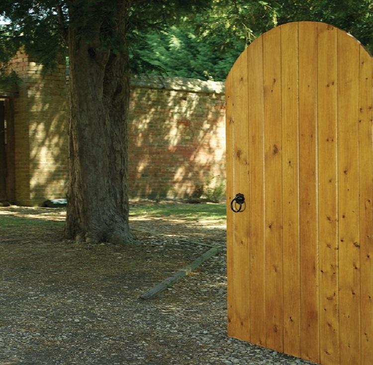 Devon arched wooden garden gate set within a pathway