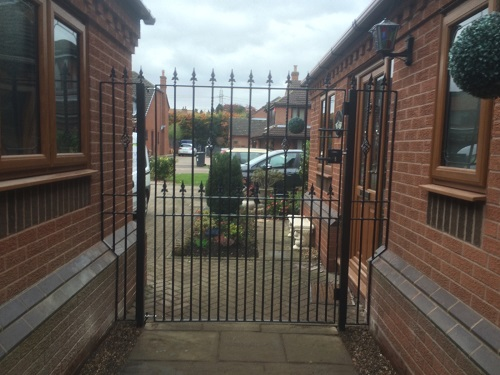 Hampton wrought iron side gate with metal infill panels securing passageway