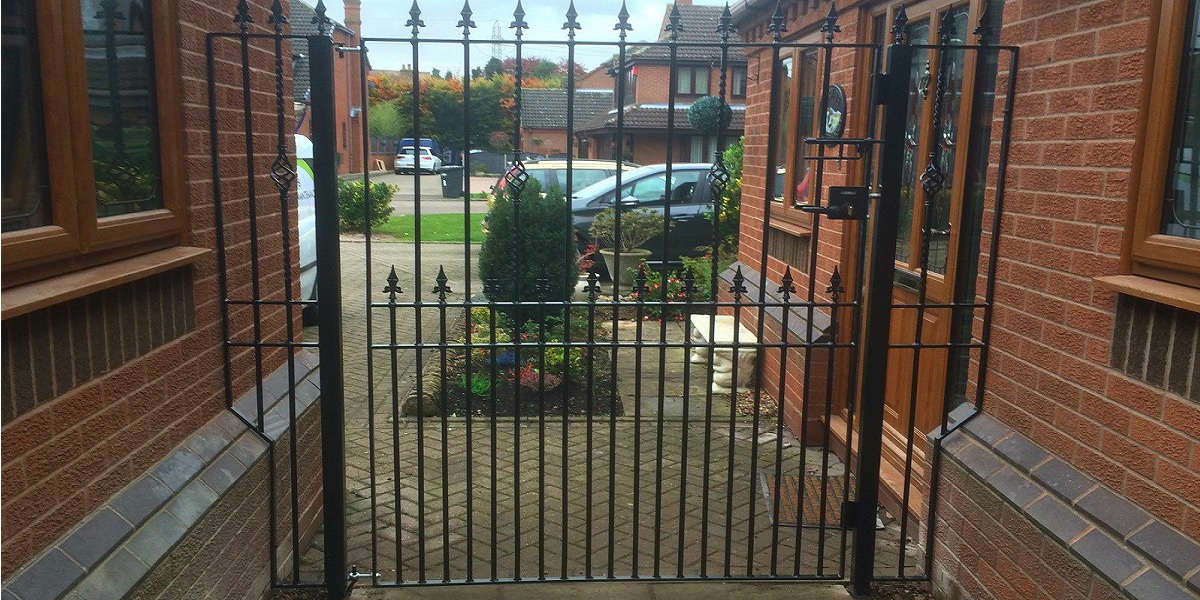 Bespoke wrought iron side garden gate with lock and metal infill panels at the side