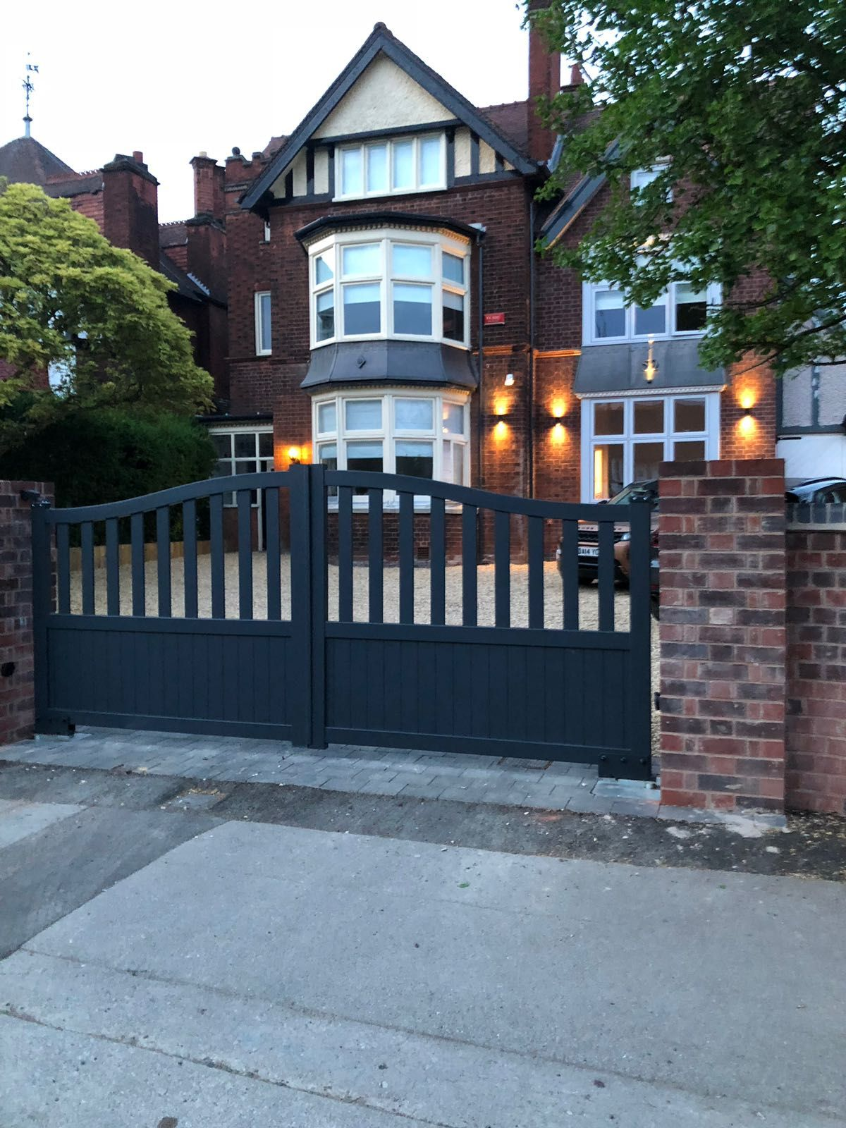 Open infill aluminium driveway gates fitted to entrance of large Victorian property