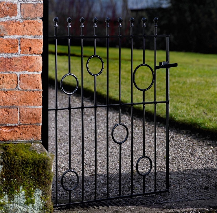 Picasso ball top modern metal garden gate fitted to a brick wall