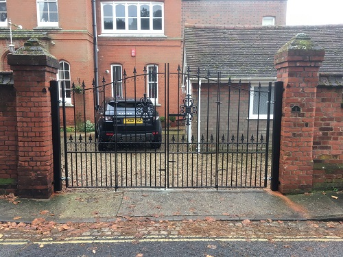 Wrought iron bi folding gates fitted to wall mounted posts